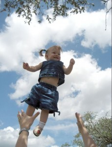 Toddler girl thrown in the air